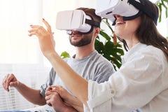 Vrouw en man in VR-beschermende brillen die handen houden en in ruimte oriënteren Stock Foto
