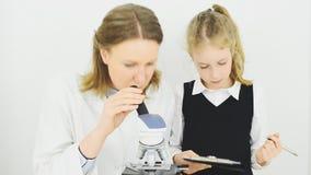 Vrouw en meisje die microscoop gebruiken stock video