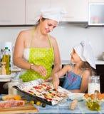 Vrouw en meisje die pizza thuis maken Royalty-vrije Stock Afbeeldingen