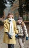 Vrouw en meisje die togther in de herfstpark lopen stock afbeelding