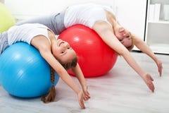 Vrouw en meisje die uitrekkende oefeningen doen Stock Foto