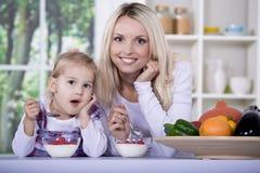 Vrouw en meisje met yoghurtkom stock afbeelding