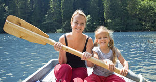 Vrouw en meisje op het meer in een kleine boot royalty-vrije stock afbeelding