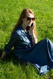 Vrouw en mobiele telefoon, groen gazon, de zomer Rood haarmeisje, blauwe kleding, die buiten op het gras zitten die, een telefoon Stock Foto