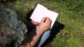 Vrouw en studenten de zitting op gras, neemt nota's in notitieboekje, lerend en schrijft gedachten, schrijft boek stock footage