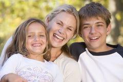 Vrouw en twee jonge kinderen die in openlucht lachen Stock Afbeeldingen