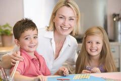 Vrouw en twee jonge kinderen in keuken met kunst p Stock Fotografie