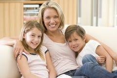 Vrouw en twee jonge kinderen in woonkamer stock afbeeldingen