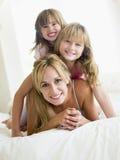 Vrouw en twee jonge meisjes in bed het spelen stock afbeeldingen