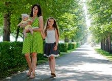 Vrouw en twee kinderen die onderaan de weg lopen Stock Afbeelding