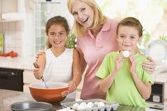 Vrouw en twee kinderen in keukenbaksel Stock Fotografie