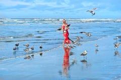 Vrouw en zeemeeuwenvogels op strand door het overzees stock foto