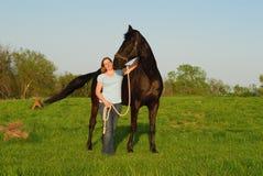Vrouw en zwart paard Royalty-vrije Stock Foto's