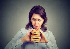 Vrouw eten die naar een smakelijke drievoudige hamburger hunkeren Royalty-vrije Stock Afbeelding
