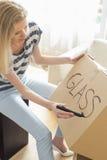 Vrouw etiketterings bewegende doos met glasmateriaal thuis royalty-vrije stock foto
