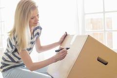 Vrouw etiketterings bewegende doos thuis stock foto's