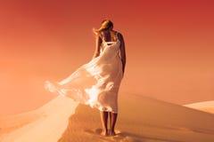 Vrouw in fladderende kleding Woestijn en Zandduinen Rode hemel royalty-vrije stock foto's