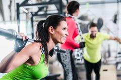 Vrouw in functionele opleiding het opheffen gewichten in gymnastiek stock afbeelding