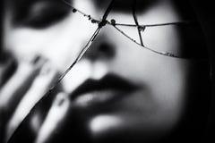 Vrouw in gebroken spiegel wordt weerspiegeld die stock foto