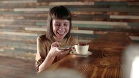 Vrouw gebruikend app op smartphone in koffie gelukkige gelaatsuitdrukking en texting op mobiele telefoon Mooie multiculturele jon stock video
