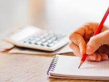 Vrouw gebruikend calculator en thuis denkend over kosten op bureaubureau royalty-vrije stock foto's