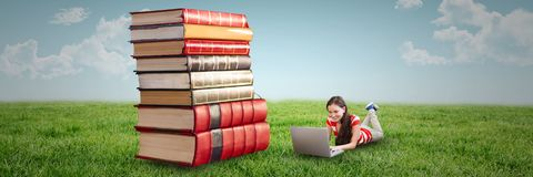 Vrouw gebruikend computer en in openlucht leggend op de vloer naast een stapel van boeken stock afbeeldingen