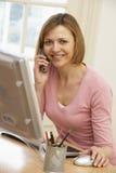 Vrouw Gebruikend Computer en Sprekend op Telefoon Stock Fotografie