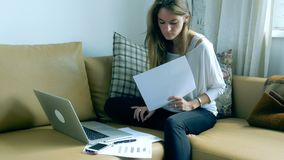 Vrouw gebruikend laptop en werkend met documenten stock videobeelden