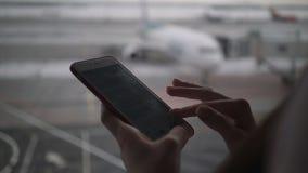 Vrouw gebruikend mobiele telefoon bij luchthaventerminal en wachtend op het inschepen van het vliegtuig stock videobeelden