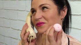 Vrouw gebruikend retro telefoon en etend koekje stock video