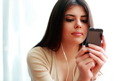 Vrouw gebruikend smartphone en luisterend de muziek Royalty-vrije Stock Afbeeldingen