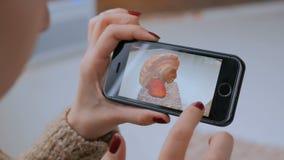 Vrouw gebruikend smartphone met vergrote werkelijkheid app en onderzoekend virtueel model stock footage