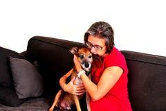 Vrouw geknuffel met hond op een grijze bank stock fotografie