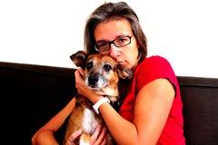 Vrouw geknuffel met hond op een grijze bank royalty-vrije stock foto's