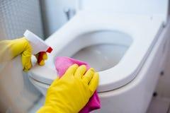 Vrouw in gele rubberhandschoenen die toilet schoonmaken stock afbeeldingen