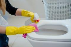 Vrouw in gele rubberhandschoenen die toilet schoonmaken royalty-vrije stock fotografie