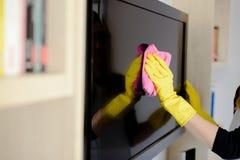 Vrouw in gele rubberhandschoenen die TV schoonmaken royalty-vrije stock fotografie