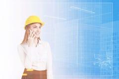 Vrouw in gestemde bouwvakker en blauwdruk, Royalty-vrije Stock Afbeeldingen