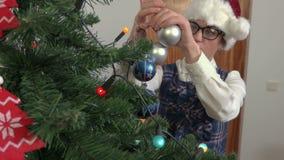 Vrouw gezette Kerstmisdecoratie op sparren stock video