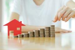 Vrouw gezette muntstukken aan stapel van muntstukken en rood huis Stock Foto