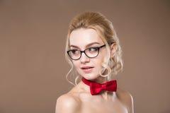 Vrouw in glazen met rode vlinder op haar hals Stock Foto