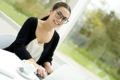 Vrouw glimlachen die aan laptop werken Stock Foto