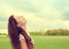 Vrouw glimlachen die omhoog aan blauwe hemel kijken die genietend van vrijheid vieren stock foto's