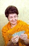 Vrouw glimlachen, die speelkaarten bekijken Stock Afbeeldingen