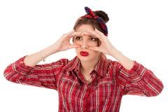 Vrouw gluren die door vingers zoals verrekijkers kijken stock fotografie