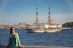 Vrouw in groene kleding en een sweater, die glazen op de achtergrond van rivier en schip op zonnige dag in St Peterburg, Rusland  Stock Foto's