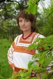 Vrouw in haar tuin vnatsionalnom kostuum Stock Foto