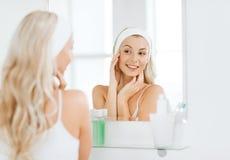 Vrouw in hairband wat betreft haar gezicht bij badkamers stock fotografie