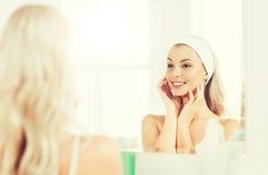 Vrouw in hairband wat betreft haar gezicht bij badkamers stock afbeeldingen