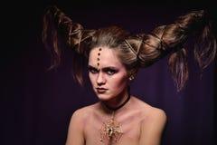 Vrouw in Halloween-make-up met kapsel in vorm van hoornen, Duivelskoningin royalty-vrije stock afbeelding